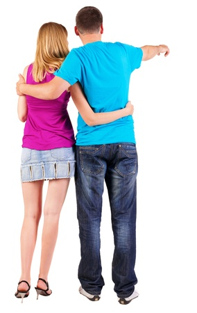 Back view of young couple pointing at wall (woman and man) in the jeans and blue T-shirt and the girl in dress.  photo