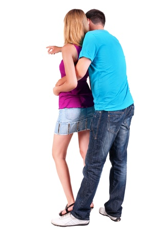 Back view of young couple pointing at wall (woman and man). guy in the jeans and blue T-shirt and the girl in dress. looking into the distance. Rear view people collection.   backside view of person.  Isolated over white background. Stock Photo