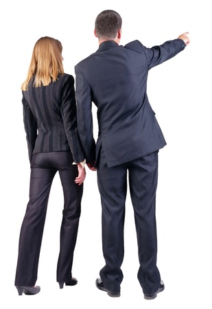 woman pointing: Back view of  pointing business team. young couple (man and woman) . beautiful friendly girl and guy in suit together. Rear view people collection. backside view of person. Isolated over white background Stock Photo