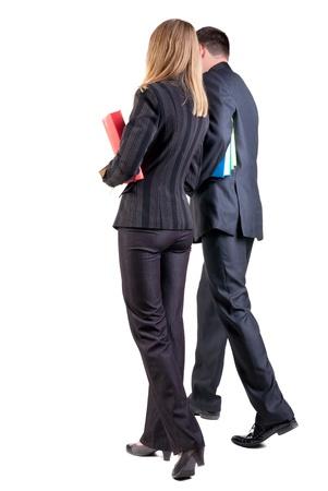 Rückansicht des Gehens Business-Team. Gehen junges Paar (Mann und Frau) mit Bücher. schöne freundliche Mann und Frau in Anzug zusammen. Rückansicht Menschen Kollektion. Rückansicht der Person. Isolierte über weißem Hintergrund