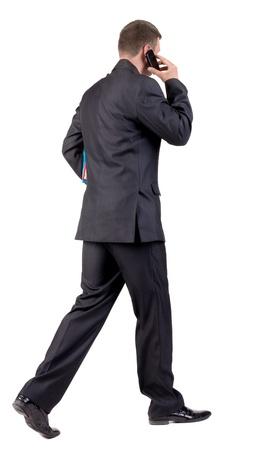 caminando: Vista posterior de la marcha del hombre de negocios con los libros. vamos hombre joven en traje negro hablando por tel�fono m�vil. Aislado sobre fondo blanco. Vista posterior recogida de las personas. trasero vista de la persona