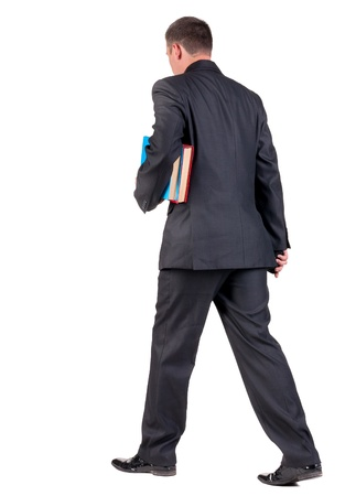 back view of walking  business man with books. going young guy in black suit. Isolated over white background. Rear view people collection. backside view of person photo