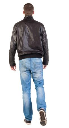 persona caminando: Vista posterior de caminar hombre guapo en la chaqueta. vamos hombre joven en pantalones vaqueros y chaqueta. Vista posterior recogida de las personas. trasero vista de la persona. Aislado sobre fondo blanco. Foto de archivo