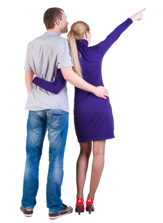 side pose: young couple pointing at wal Back view  (woman and man). guy in the jeans shirt and  girl in blue dress looking into the distance. Rear view people collection.  backside view of person.  Isolated over white background.