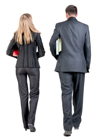 treading: Back view of walking business team. Going young couple (man and woman) with books. beautiful friendly girl and guy in suit together. Rear view people collection. backside view of person. Isolated over white background Stock Photo