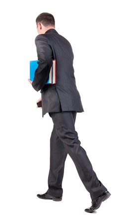 striding: back view of walking  business man with books. going young guy in black suit. Isolated over white background. Rear view people collection. backside view of person Stock Photo
