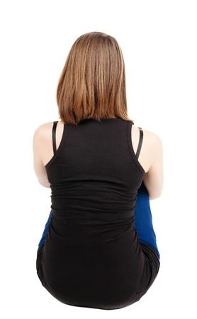 床に座って美しい若い女性の背面し、の距離に見えます。ブロンドの女の子を緩和します。背面ビューの人々 のコレクションです。人の裏面の表示
