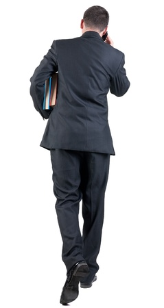 back view of walking  business man with books. going young guy in black suit talking on mobile phone. Isolated over white background. Rear view people collection. backside view of person photo