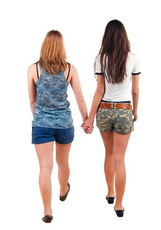 Back view going of two young girl (brunette and blonde)  . Rear view people collection.  backside view of person. beautiful woman friends  walking. Rear view. Isolated over white background.   photo