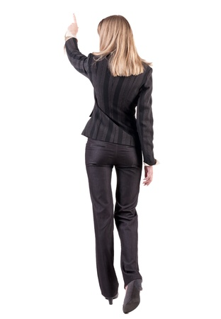 backwards: Back view of  business woman walking and pointing  young businesswoman in black suit  Rear view people collection   backside view of person   Isolated over white background