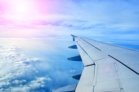 airliner: Wing of an airplane flying above the clouds  people look at the sky from the window of the plane, using air transport to travel  backlight sun beam