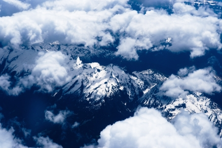 Mountain view from the top through the clouds    The mountain peaks covered with snow  View from airplane  blue tint photo