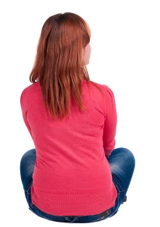 relaxes: Vista trasera de una mujer joven hermosa en los pantalones vaqueros que se sientan y se ve en la distancia. La muchacha rubia se relaja. Vista posterior recogida de las personas. vista trasera de su persona. Aislado sobre fondo blanco.