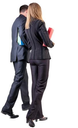 businesswoman suit: Vista posterior de caminar equipo de negocios. Yendo joven pareja (hombre y mujer) con los libros. hermosa chica amable y hombre en traje juntos. Vista posterior recogida de las personas. vista trasera de su persona. Aislado sobre fondo blanco Foto de archivo
