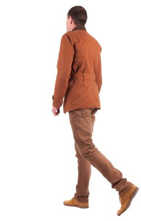 personas de espalda: Volver la vista de hombre va elegantemente vestido con una chaqueta marrón. caminando chico joven. Vista posterior recogida de las personas. vista trasera de su persona. Aislado sobre fondo blanco.