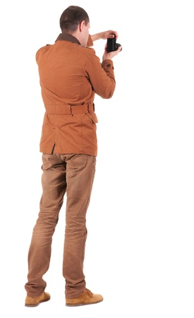 backside: Back view of man photographing.   stylishly dressed in casual clothes photographer. Rear view people collection.  backside view of person.  Isolated over white background. Stock Photo