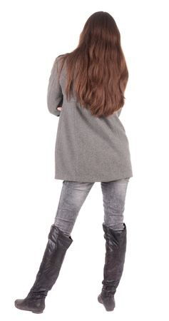 side pose: back view of standing young beautiful  woman.  brunette girl in jeans and coat watching;. Rear view people collection.  backside view of person.  Isolated over white background.