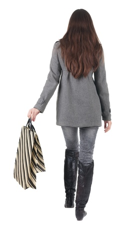 back view of going  woman  with shopping bags. beautiful brunette girl in motion.  backside view of person.  Rear view people collection. Isolated over white background. photo