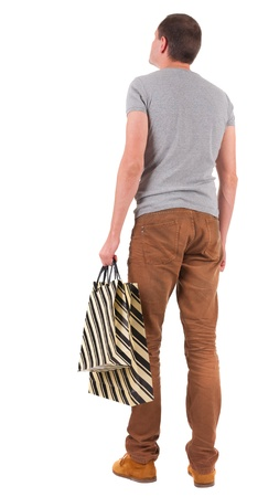 Back view of handsome manwith shopping bags  looking up.   Standing young guy in jeans and  jacket. Rear view people collection.  backside view of person.  Isolated over white background. Stock Photo