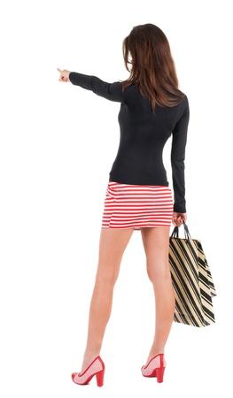 zurück zu gehen Frau im Kleid Frau mit Einkaufstüten zeigt anzuzeigen. schöne Brünette Mädchen in Bewegung. Rückansicht der Person. Rückansicht Menschen Sammlung. Isoliert auf weißem Hintergrund. Standard-Bild