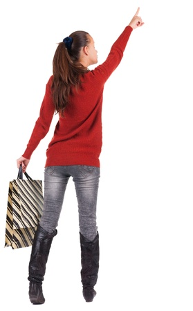 back view of  woman  in  jeans  with shopping bags pointing .   backside view of person.  Rear view people collection. Isolated over white background. photo