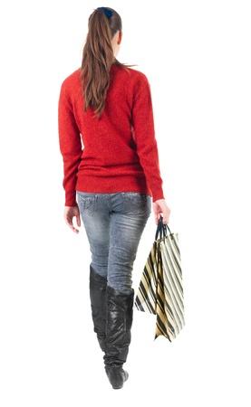 Vue arrière d'aller woman with shopping bags. belle jeune fille brune en mouvement. vue arrière de sa personne. Vue arrière gens collection. Isolé sur fond blanc.