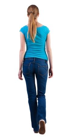 detras de: Vista posterior de caminar mujer en vaqueros y camiseta. hermosa chica rubia en movimiento. vista trasera de su persona. Vista posterior recogida de las personas. Aislado sobre fondo blanco. Foto de archivo