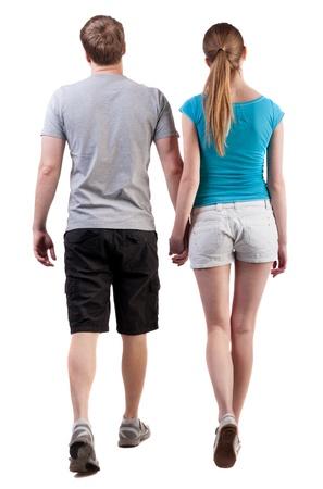 personas caminando: Vista posterior de ir joven pareja (hombre y mujer). caminando hermosa chica amable y hombre en pantalones cortos juntos. Vista posterior recogida de las personas. vista trasera de su persona. Aislado sobre fondo blanco. Foto de archivo