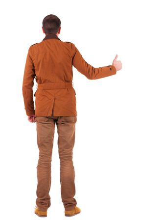 Back view of  man in jacket  shows thumbs up.   Rear view people collection.  backside view of person.  Isolated over white background. photo