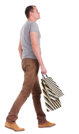 Back view of walking   man in gray shirt with shopping bags.  going young guy . Rear view people collection.  backside view of person.  Isolated over white background. photo