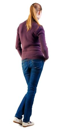 back view of standing young beautiful  blonde woman. girl in jeans and sweater watching. Rear view people collection.  backside view of person.  Isolated over white background. photo