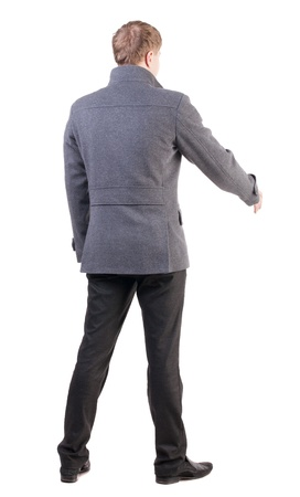 back view of businessman in coat reaches out to shake hands. secured a man who welcomes you. Rear view people collection. backside view of person. Isolated over white background. photo