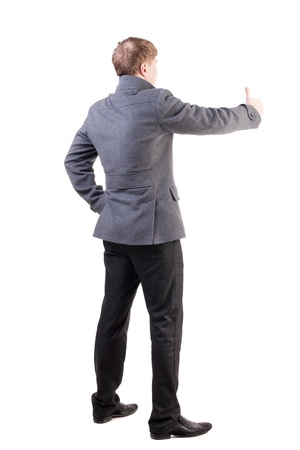 Back view of  business man in coat shows thumbs up.   Rear view people collection. cheerful office worker shows positive emotions.  backside view of person. confident man in autumn clothes positive gestures.  Isolated over white background. photo