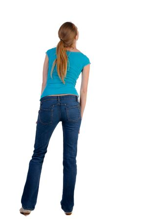 curiously: back view of standing young beautiful  blonde woman in blue t-shirt and jeans. girl  watching. Rear view people collection.  backside view of person. she curiously looks up.  Isolated over white background.