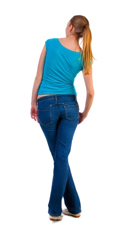 back view of standing young beautiful  blonde woman in blue t-shirt and jeans. girl looks in a relaxed position in  side. girl  watching. Rear view people collection.  backside view of person.  Isolated over white background. photo