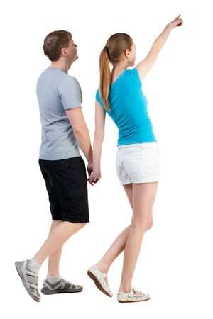 Back view of walking young couple (man and woman) pointing. curious wife shows her husband attractions. Rear view people collection. backside view of person. Isolated over white background photo