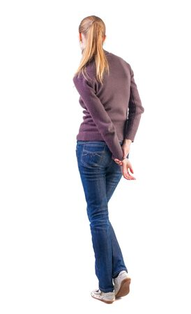 back view of standing young beautiful  blonde woman. girl in jeans and sweater watching.shy girl waits. Rear view people collection.  backside view of person.  Isolated over white background. photo