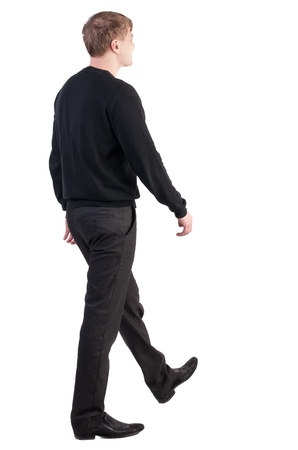back view of walking  business man.  blond smiling man in a sweater and pants goes to the right. stylishly dressed in formal wear young man. Isolated over white background. Rear view people collection.  backside view of person.