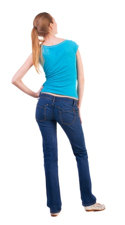 back view of standing young beautiful  blonde woman in blue t-shirt and jeans. girl  watching. Rear view people collection.  backside view of person. she curiously looks up.  Isolated over white background. happy teenage girl looking to the side resting h photo