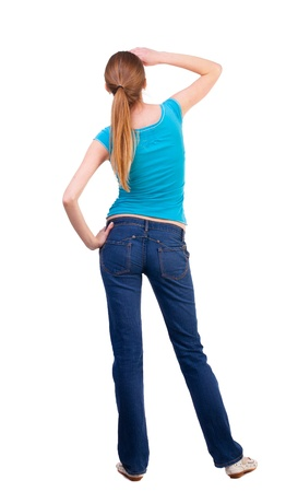 back view of standing young beautiful  blonde woman in blue t-shirt and jeans. girl  watching. Rear view people collection.  backside view of person. she curiously looks up.  Isolated over white background. curious teen girl looks at the sky a hand coveri photo