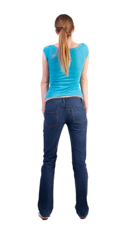 curiously: back view of standing young beautiful  blonde woman in blue t-shirt and jeans. girl  watching. Rear view people collection.  backside view of person. she curiously looks up.  Isolated over white background. Teen beauty with his hands in his jeans pocket w