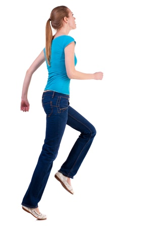 back view of running  woman  in  jeans. beautiful blonde girl in motion.  backside view of person.  Rear view people collection. Isolated over white background. she rushes to meet someone photo