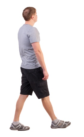ropa de verano: Vista posterior de la marcha del hombre guapo en pantalones cortos y zapatillas de deporte. Deportes Elegante hombre joven se mueve. ir joven. Vista posterior recogida de las personas. trasero vista de la persona. Aislado sobre fondo blanco. deportista en ropa de verano se quedan