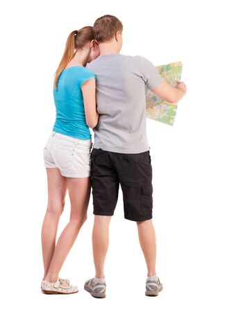Back view journey of the young couple looking at the map. Rear view people collection. husband and wife in a summer vacation  backside view of person.  Isolated over white background. a young couple on a journey in search for the right route map photo