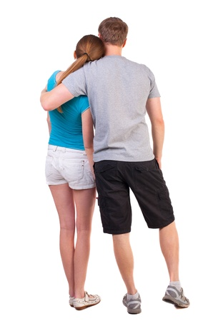 Back view of young couple (man and woman) dressed for summer travel a couple of young people. beautiful friendly girl and guy together. Rear view. Isolated over white background. Sports heterosexual couple hugging in summer shorts Imagens