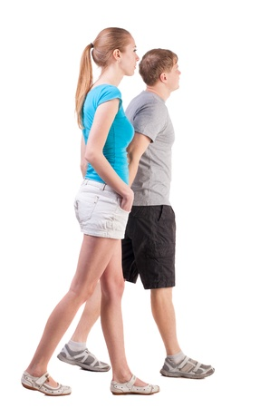 Back view of going young couple (man and woman). walking beautiful friendly girl and guy in shorts together. Rear view people collection. backside view of person.  Isolated over white background. the couple went off arm in arm photo