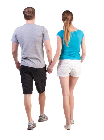 Back view of going young couple (man and woman). walking beautiful friendly girl and guy in shorts together. Rear view people collection. backside view of person.  Isolated over white background. Tourists walk somewhere photo