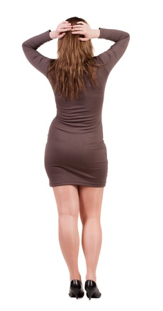 Back view of shocked business woman in dress .   upset young girl. Rear view people collection.  backside view of person.  Isolated over white background. Brunette in brown dress holding his head experiencing photo