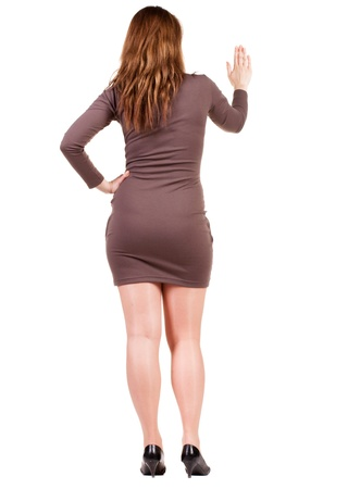 bisiness:  back view of Businesswoman . Young bisiness woman in dress presses down on something. Isolated over white background. Rear view people collection. backside view of person. she holds his hand open, palm forward