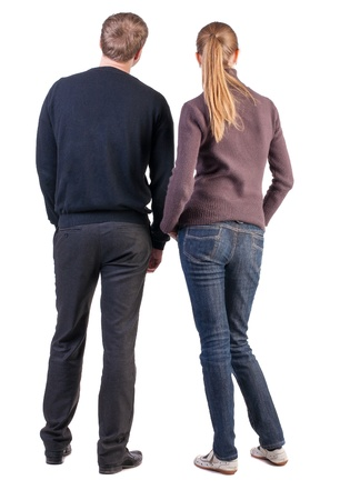 Back view of young couple (man and woman) hug and look into the distance. beautiful friendly girl and guy together. Rear view. Isolated over white background. a boy and a girl from opposite-sex couples face with his hands in his pockets and looking at som